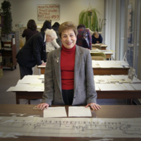 Penny Petrone posing in front of her collection of papers she gifted to the Chancellor Paterson Library