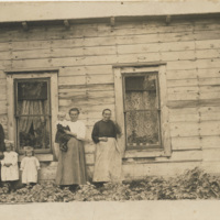 Family standing in front of a farm house